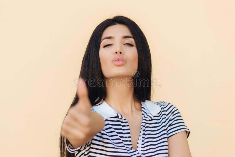Den bot för ` s! Den älskvärda sunda kvinnlign med mörkt hår, blickar säkert på kameran, lönelyfttumme som visar som gest, godkän royaltyfria bilder