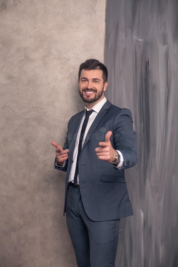 Den bra seende stiliga lyckliga affärsmannen står i hans kontor som pekar fingrar till kameran och le bärande dräkt och a arkivfoto