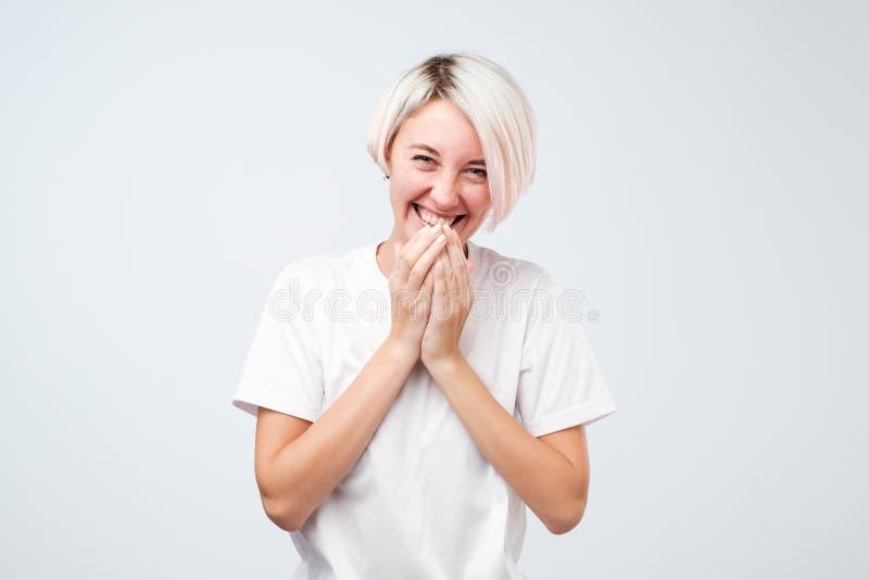 Den bra seende unga kvinnlign med färgade bärande vita t-skjorta för hår fniss joyfully, räkningar skvallrar, som försök stoppar  arkivbild