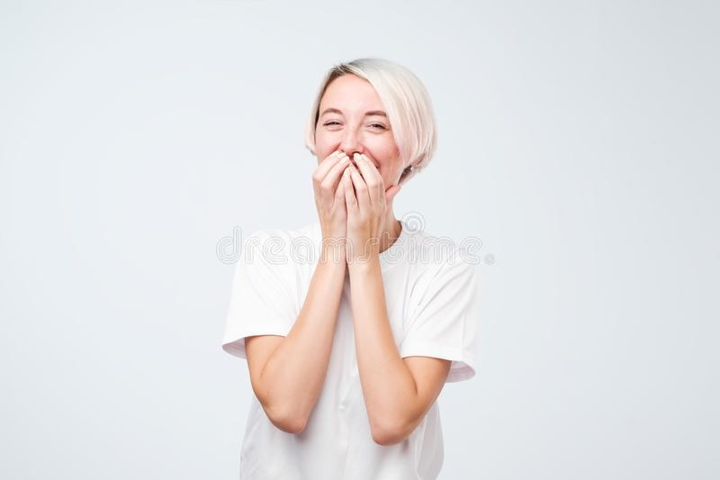 Den bra seende unga kvinnlign med färgade bärande vita t-skjorta för hår fniss joyfully, räkningar skvallrar, som försök stoppar  royaltyfri fotografi