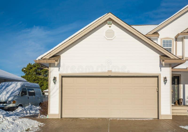Den breda garagedörren av det lyxiga huset med den konkreta körbanan och RV-vagnen parkerade närliggande arkivbilder