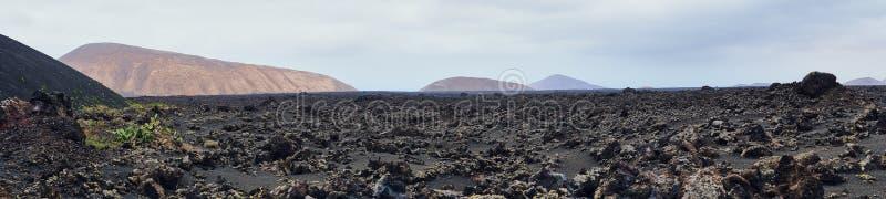 Den breda panoramabilden av det vulkaniskt vaggar i den Timanfaya nationalparken arkivbild