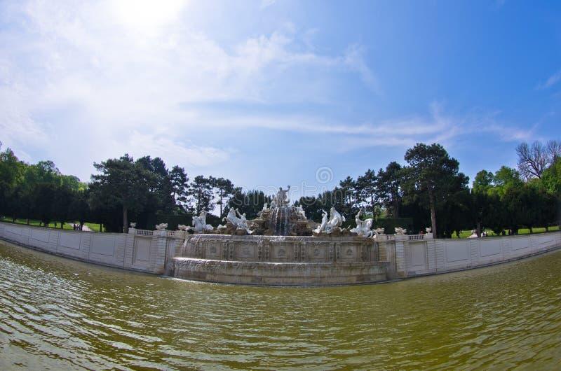 Den breda sikten av Neptunspringbrunnen av Schenbrunn parkerar framme och slotten i Wien arkivfoto