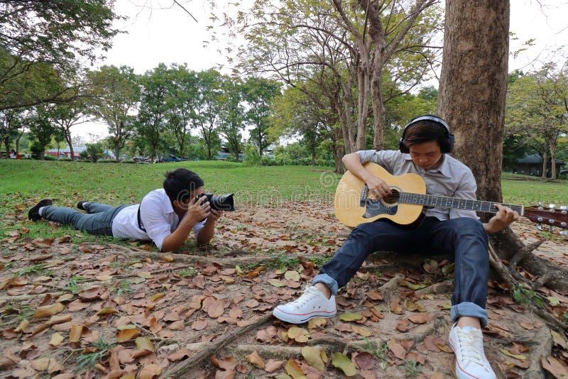 Den breda vinkeln sköt av fotografen som tar ett foto av den avkopplade unga mannen med hörlurar som spelar den akustiska gitarre royaltyfri bild