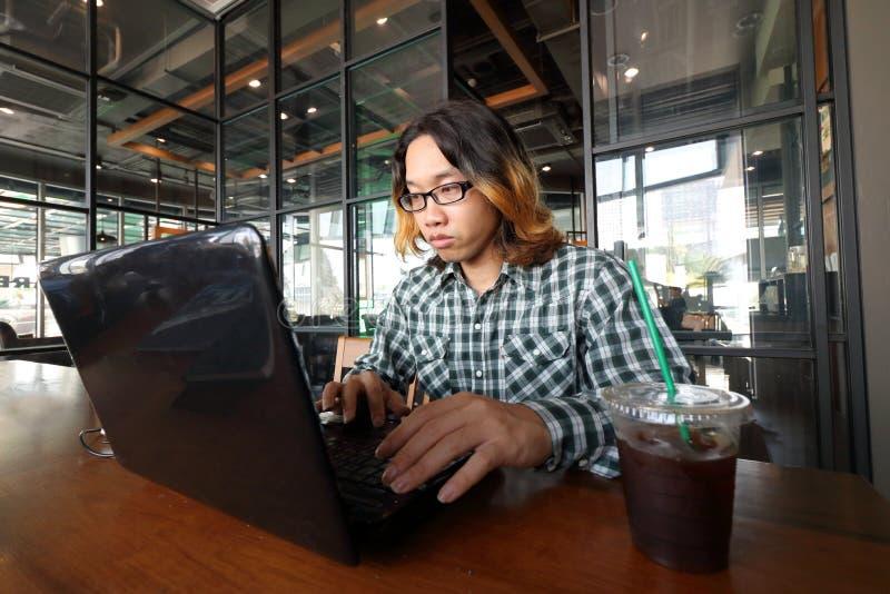 Den breda vinkeln sköt av den unga asiatiska hipstermannen som arbetar mot bärbara datorn i hans kontor fotografering för bildbyråer