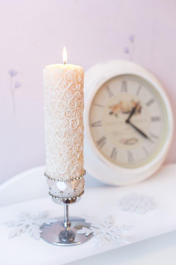 Den brinnande stearinljuset och den vita klockan royaltyfria foton