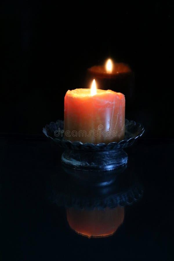 Den brinnande stearinljuset reflekterar i mörkret arkivbilder