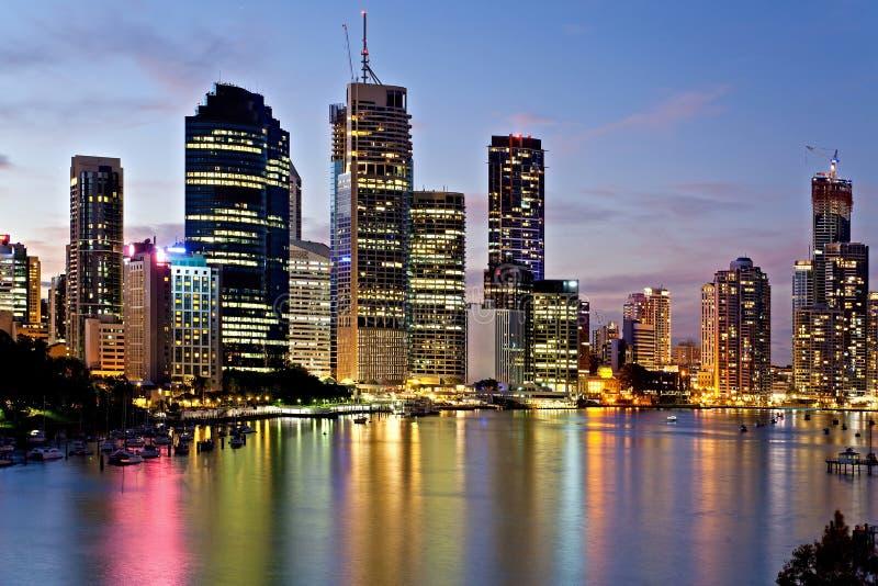 Den Brisbane staden reflekterade i floden på natten arkivfoto