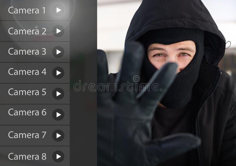 Den brottsliga mannen på manöverenhet för App för säkerhetskameran shoppar framdelen arkivbild
