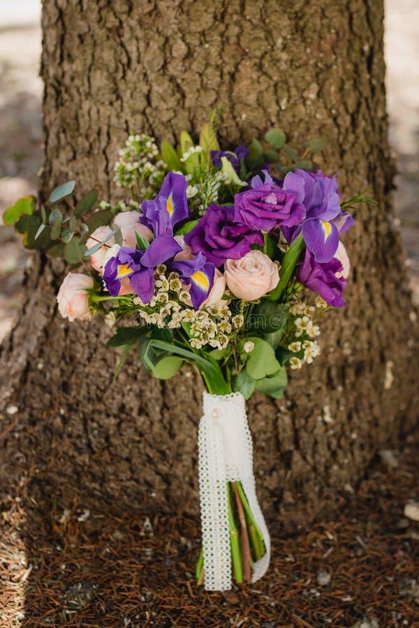 Den brud- buketten av bruden med lilablommor ligger på en stol arkivfoto