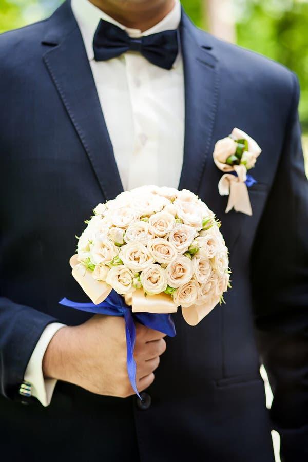 Den brud- buketten i händer som gifta sig buketten i händer av brudgummen, ansar morgonen, affärsmannen, bröllop, mode för man` s arkivfoton