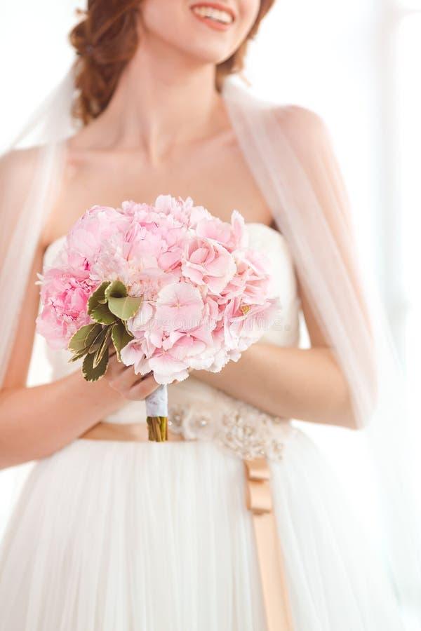 Den brud- buketten som är härlig av rosa bröllop, blommar i händer av bruden arkivbilder
