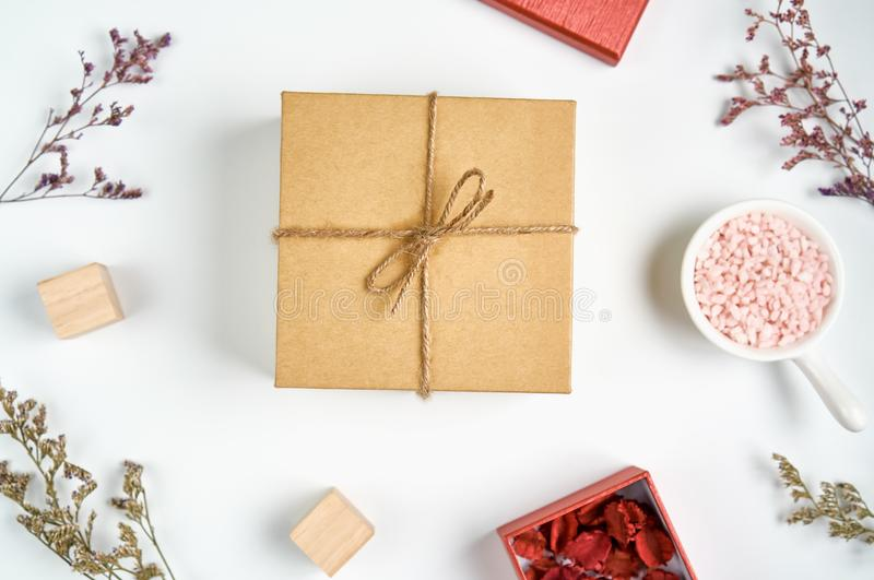 Den bruna gåvaasken med flugan och gräsblomman med den lilla röda asken förlade sidan för att se härlig För bruk med jul eller ny arkivfoto