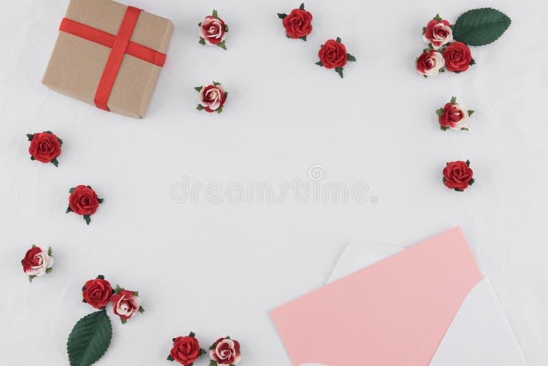 Den bruna gåvaasken och rosa färgkortet i vit packar in royaltyfria foton