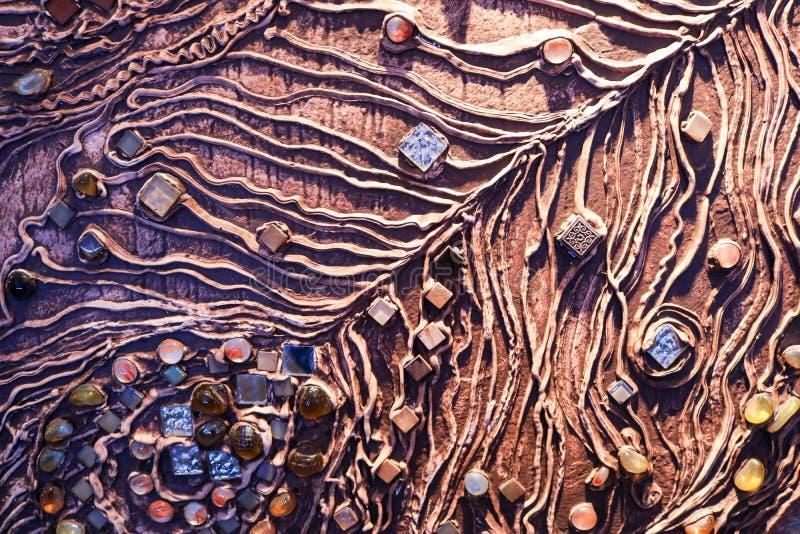 Den bruna texturen av betongväggen göras av dekorativ murbruk med tillägget av mång--färgad ädelstenar, exponeringsglasfyrkanter  arkivbild