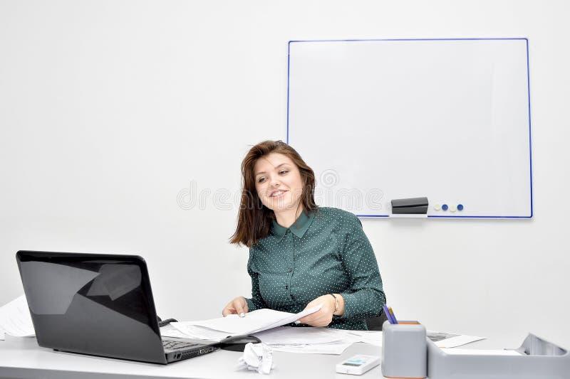 Den brunhåriga flickan framme av bärbar datorskärmen talar lyckligt på Skype Begreppet av distansutbildningen fotografering för bildbyråer