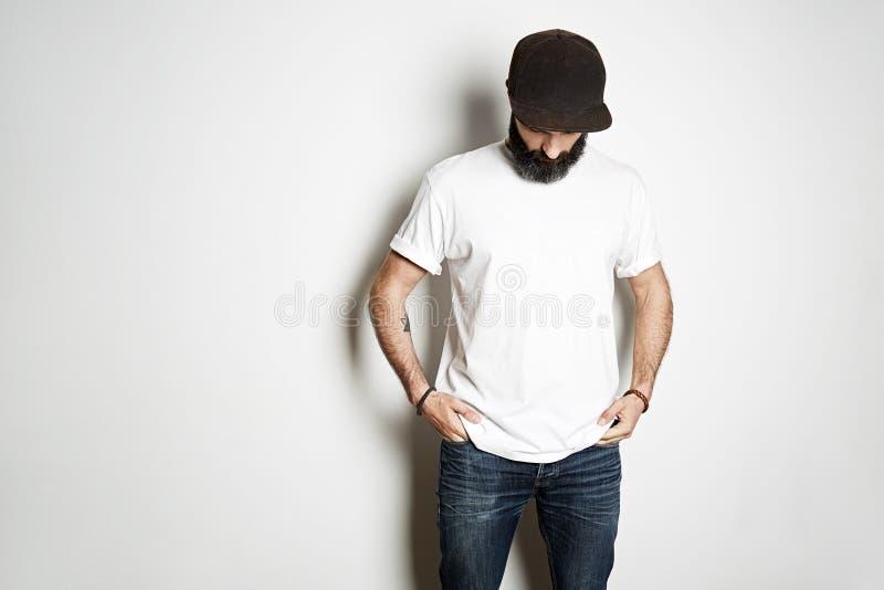 Den brutala attraktiva skäggiga cyklistmannen med tatuerade händer poserar i den vita tomma t-skjortan från högvärdig tunn bomull royaltyfri bild