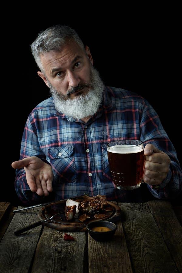 Den brutala gråhåriga vuxna mannen med ett skägg äter senapsgult biff, och drinköl, inviterar till ett mål, begreppet av en ferie royaltyfria foton