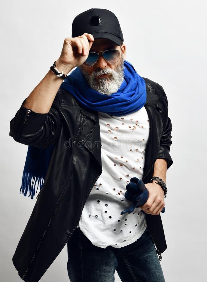 Den brutala höga rikeman i läderomslag och lång blå halsduk rymmer skärmen av hans stilfulla trendiga män för baseballmössan royaltyfria bilder