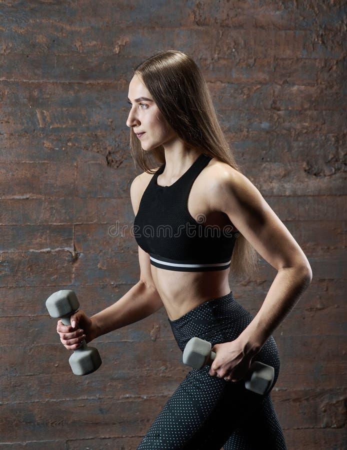 Den brutala idrotts- kvinnan som pumpar upp, tränga sig in med hantlar royaltyfria foton