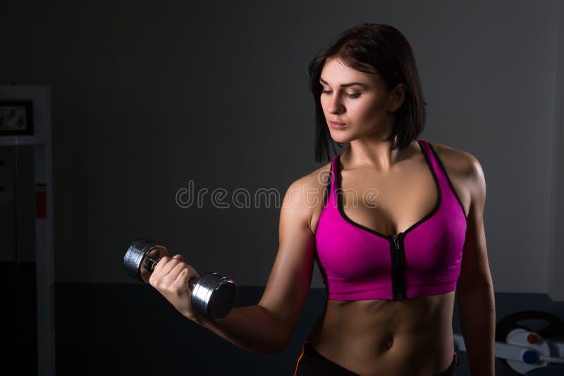 Den brutala idrotts- kvinnan som pumpar upp, tränga sig in med hantlar royaltyfria bilder