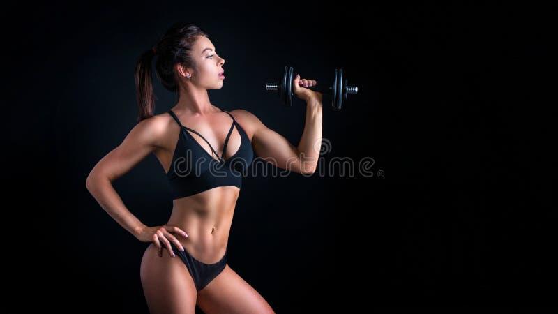 Den brutala idrotts- kvinnan som pumpar upp, tränga sig in med hantlar royaltyfri foto