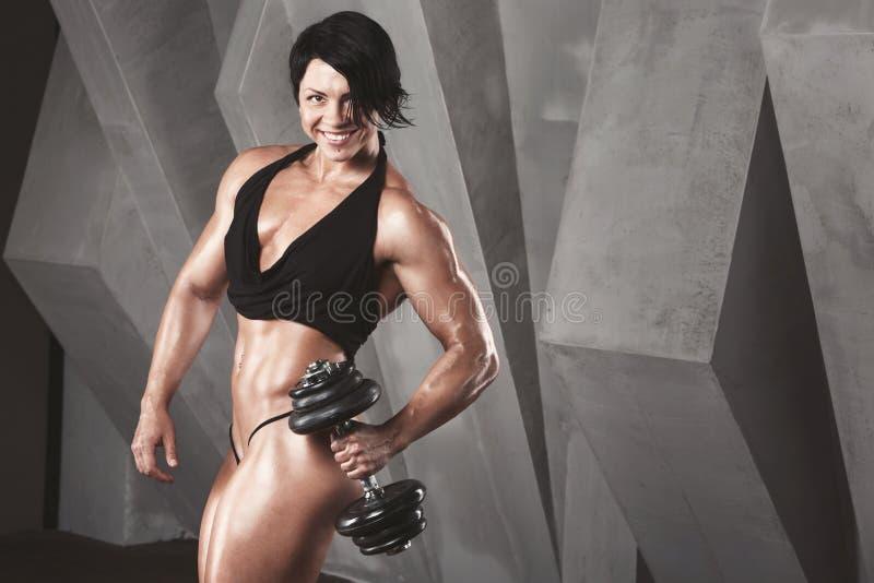 Den brutala idrotts- kvinnan som pumpar upp, tränga sig in med hantlar arkivbilder