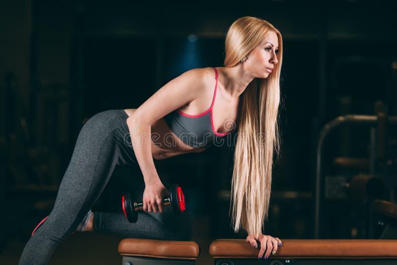 Den brutala idrotts- kvinnan som pumpar upp, tränga sig in med hantlar i idrottshall arkivbilder