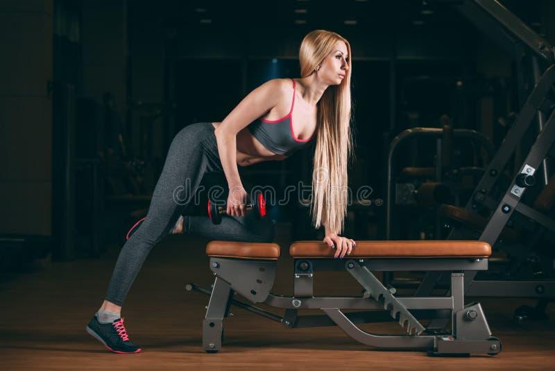 Den brutala idrotts- kvinnan som pumpar upp, tränga sig in med hantlar i idrottshall royaltyfri fotografi
