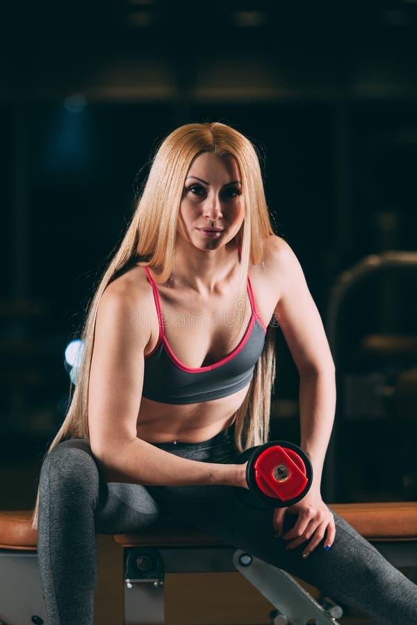 Den brutala idrotts- kvinnan som pumpar upp, tränga sig in med hantlar i idrottshall royaltyfri foto