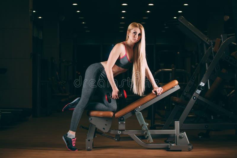 Den brutala idrotts- kvinnan som pumpar upp, tränga sig in med hantlar i idrottshall arkivfoto