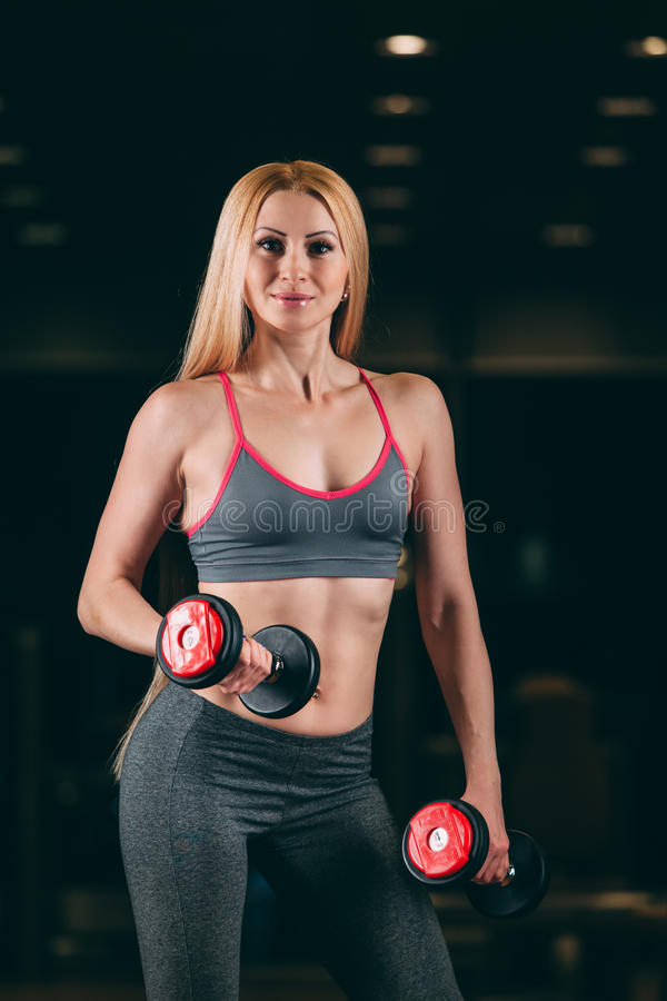 Den brutala idrotts- kvinnan som pumpar upp, tränga sig in med hantlar i idrottshall royaltyfri bild