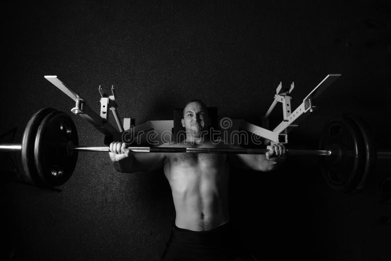 Den brutala idrotts- mannen som pumpar upp, tränga sig in royaltyfri foto