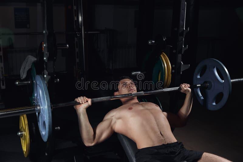 Den brutala idrotts- mannen som pumpar upp, tränga sig in på bänkpress arkivbilder
