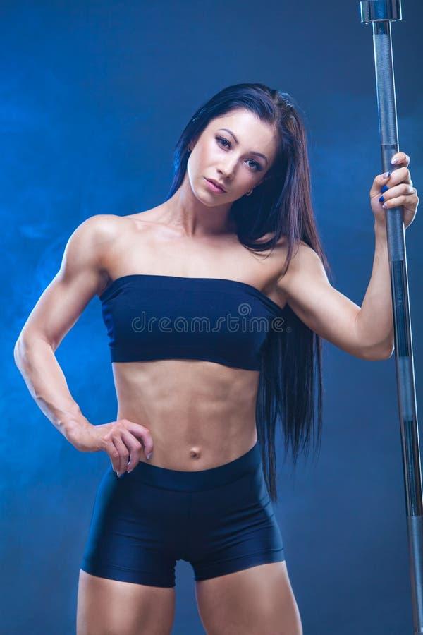 Den brutala idrotts- sexiga kvinnan rymmer en skivstång Begreppet av övningssportar som annonserar en idrottshall isolerat på en  arkivfoton
