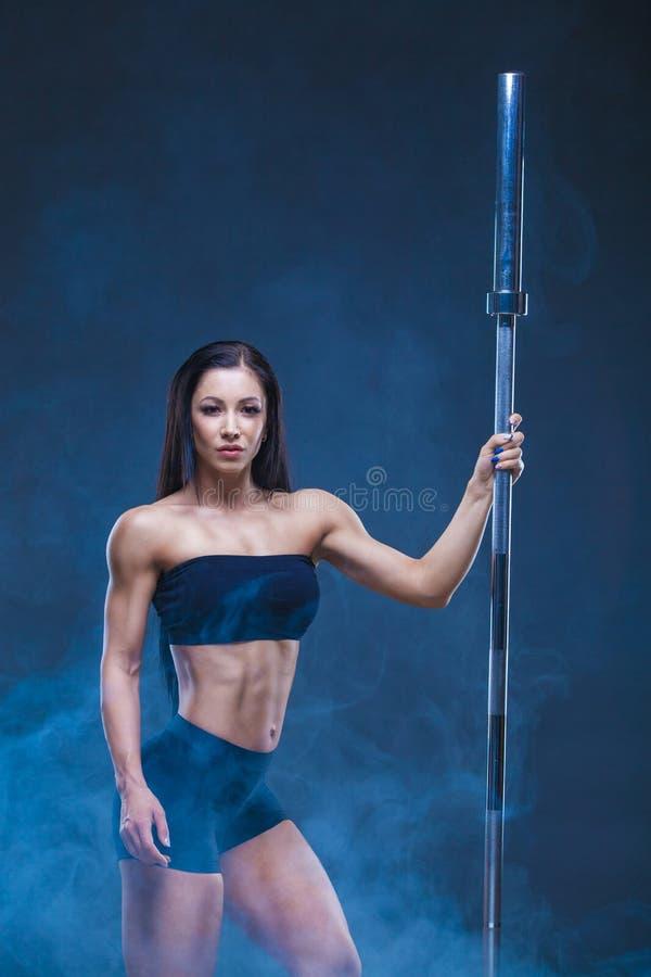 Den brutala idrotts- sexiga kvinnan rymmer en skivstång Begreppet av övningssportar som annonserar en idrottshall På en svart royaltyfria foton