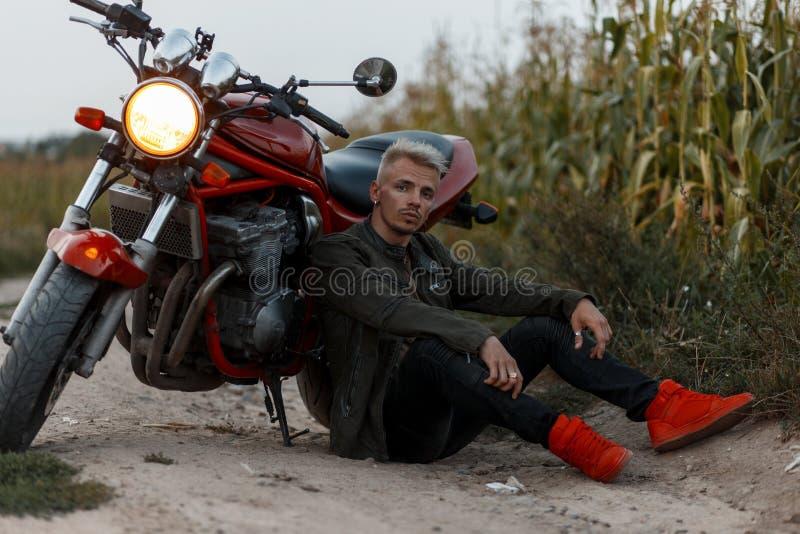 Den brutala modellmannen i en militär kaki för mode klår upp med rött royaltyfri bild