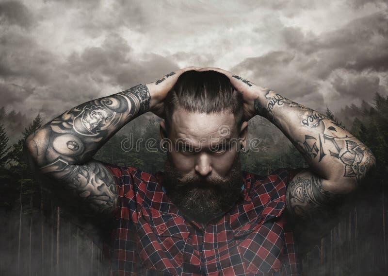 Den brutala skäggiga mannen med den tatuerade armen ser ner arkivbild