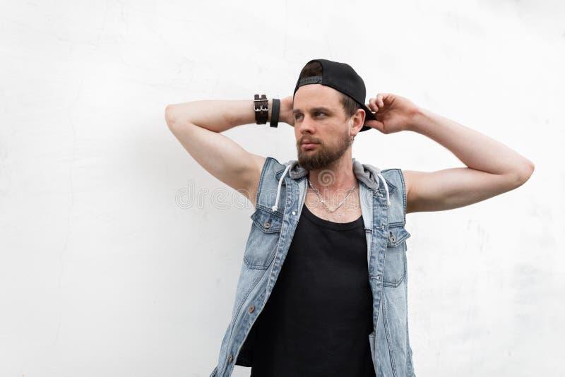 Den brutala stiliga unga hipstermannen med ett skägg i en tappningblåttgrov bomullstvill tilldelar en svart t-skjorta som poserar arkivbild