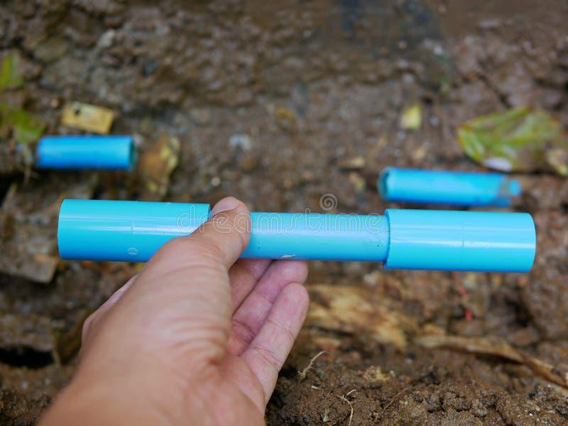 Den brutna/läckte/spruckna tunnelbanan för PVC-vattenröret ska just att fixas, genom att byta ut snitt-avdelen royaltyfri foto