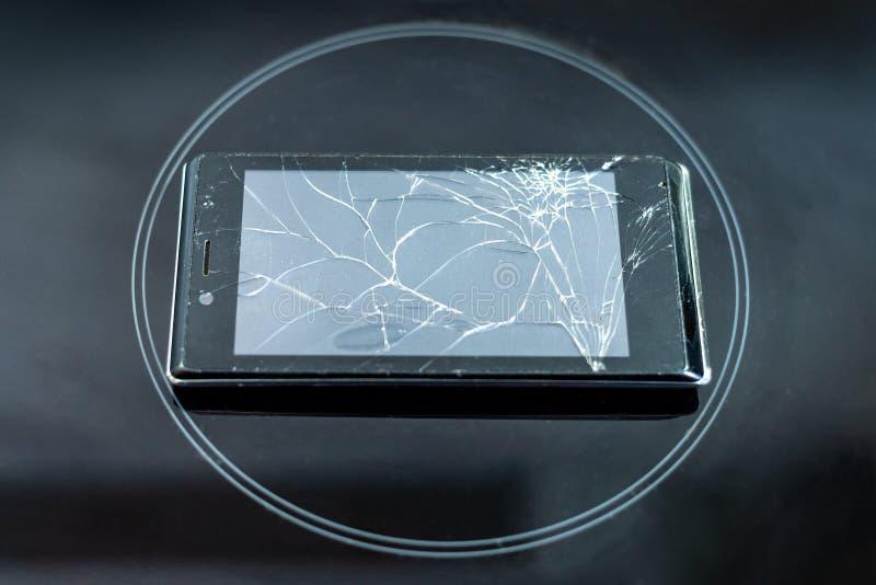 Den brutna telefonen vilar på ett svart frostat exponeringsglas, i mitten av cirkeln arkivfoton