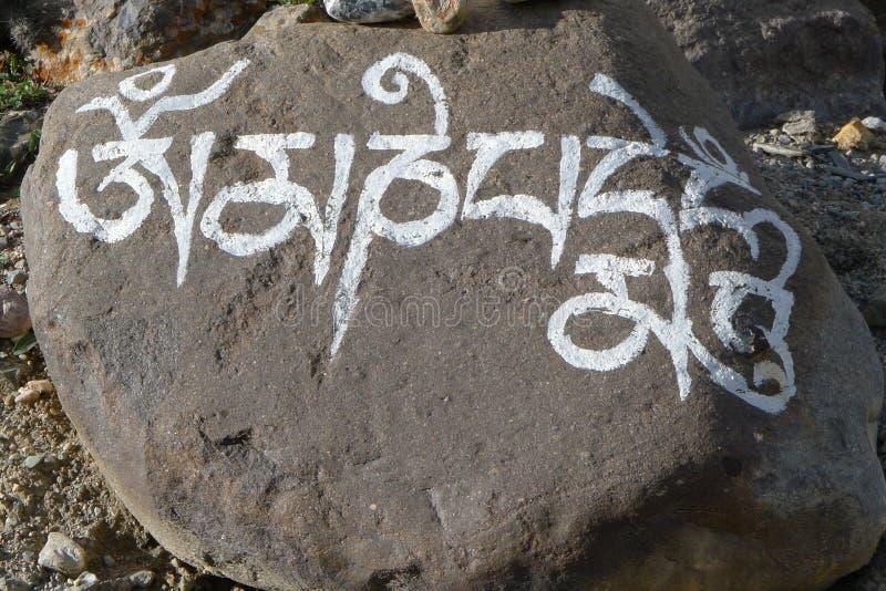 Den buddistiska mantraen Om Mani Padme Hum målade på stenen arkivbilder
