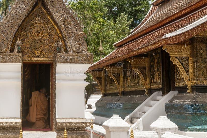 Den buddistiska munken ber att knäfalla i en relikskrin inom den Wat Xieng Thong templet i Luang Prabang, Laos royaltyfria bilder