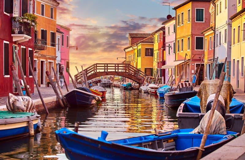 Den Burano ön i Venedig Italien den pittoreska solnedgången över kanalen med fartyg bland gamla färgglade hus stenar gator royaltyfria bilder