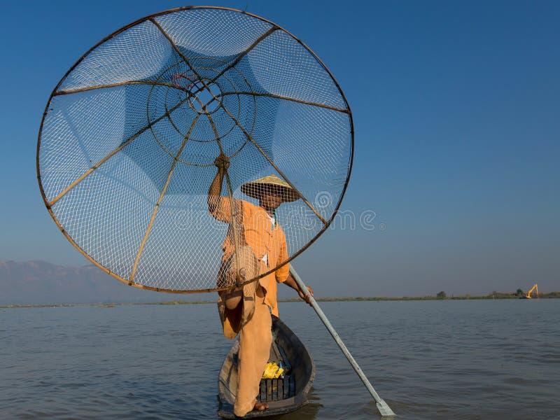 Den Burmese fiskarebenägenheten på åran som poserar i traditionell kläder med handen och foten som rymmer hans kotte, formade fis royaltyfria foton