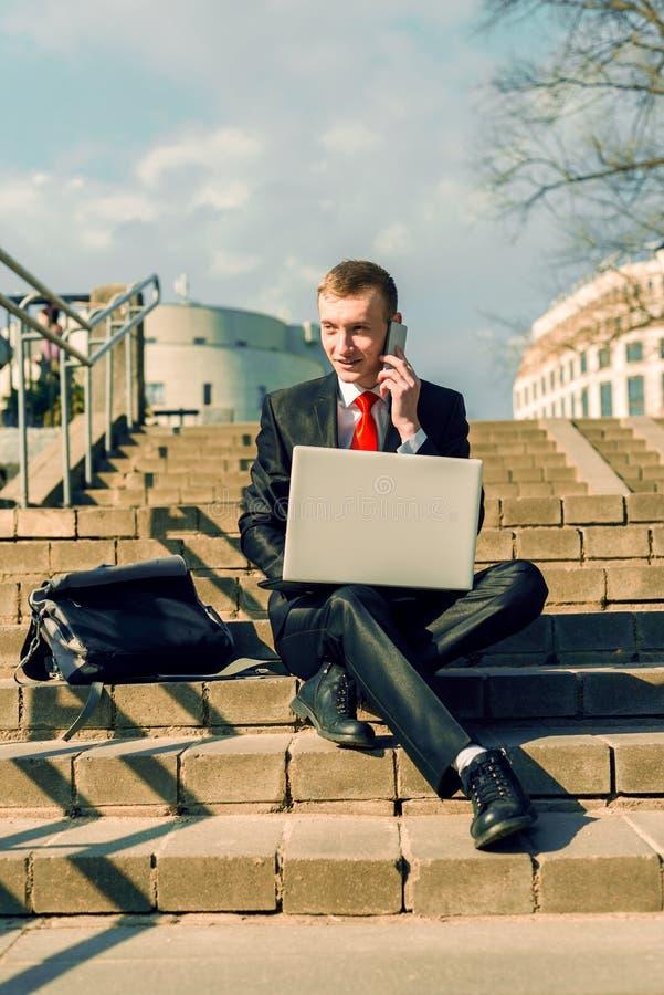 Den Businessan freelanceren arbetar i den öppna luften i staden En man i en svart dräkt och ett rött band sitter på momenten royaltyfri fotografi