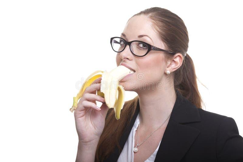 Den Businnes damen äter bananen arkivfoton
