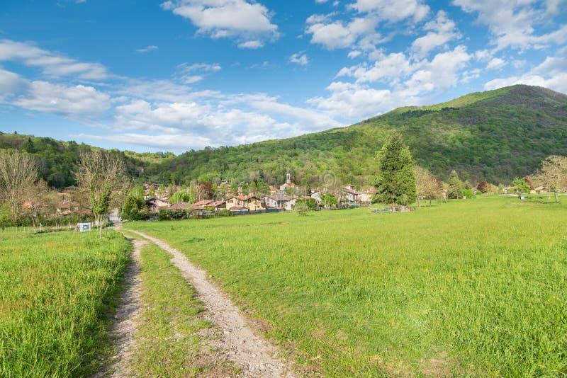Den Campo deien regionala Fiori parkerar med den Brinzio byn, nordliga Italien arkivbild