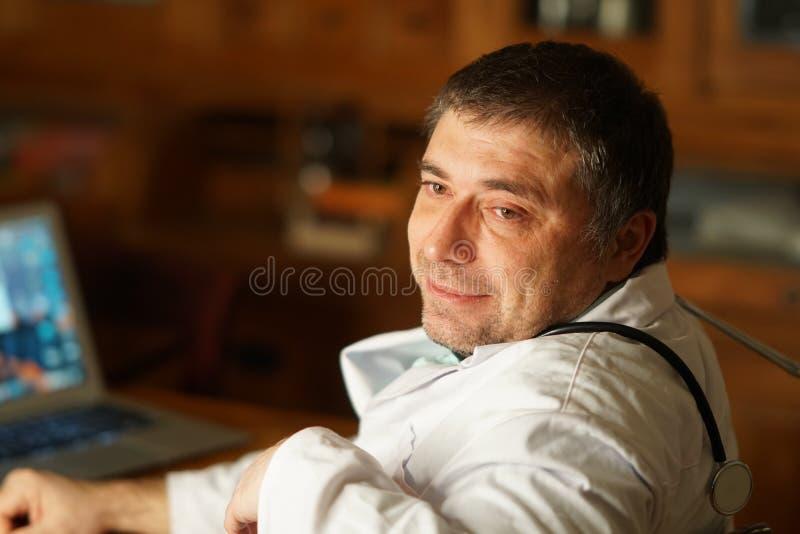 Den Caucasian doktorn på skrivbordet, tre fjärdedel poserar royaltyfri foto
