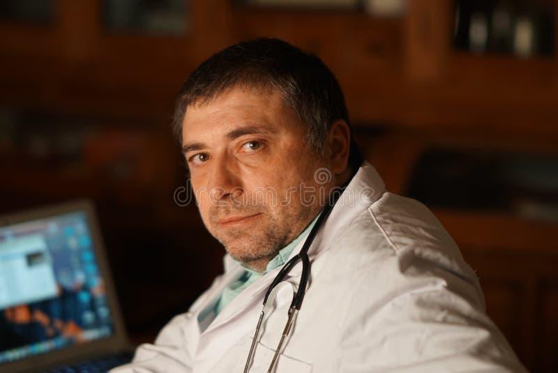Den Caucasian doktorn på skrivbordet, tre fjärdedel poserar royaltyfri bild